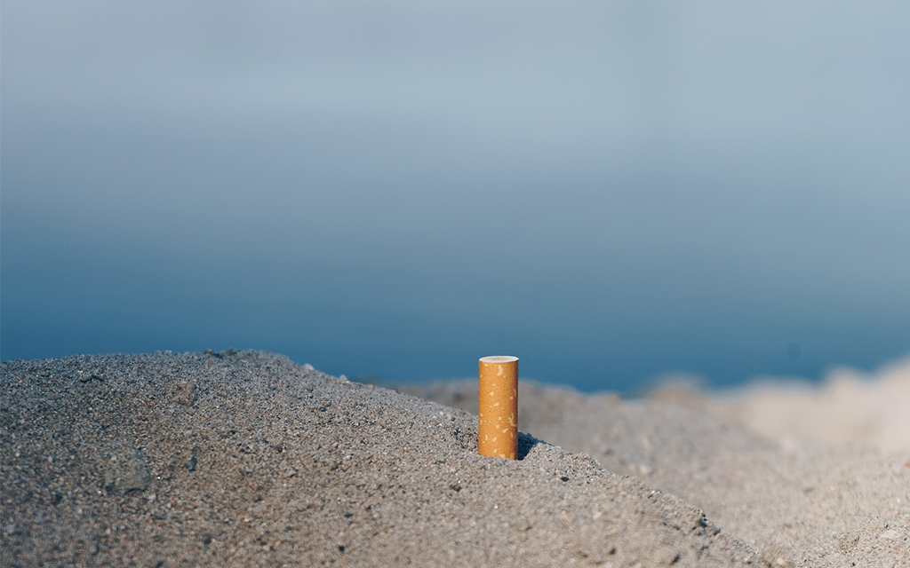 A cigarette butt sticking out of sand at the seaside.