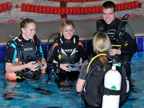 Diving instructor with students in pool