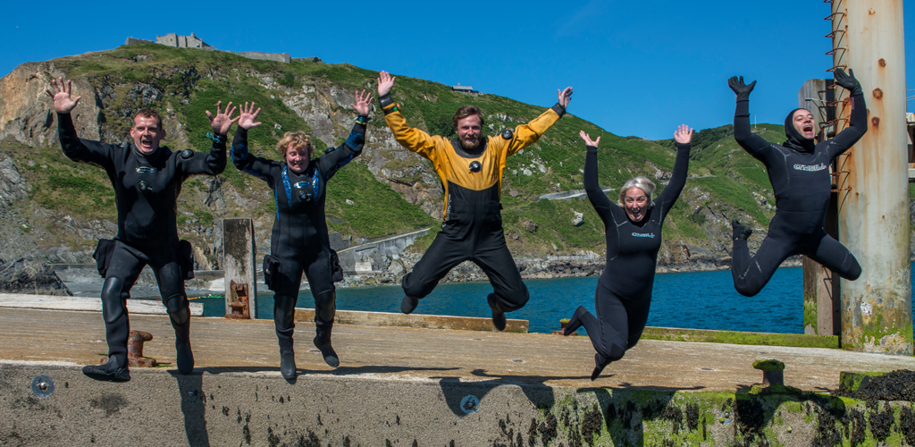 Welcome to the new BSAC website - divers jumping off harbour into water on a sunny day