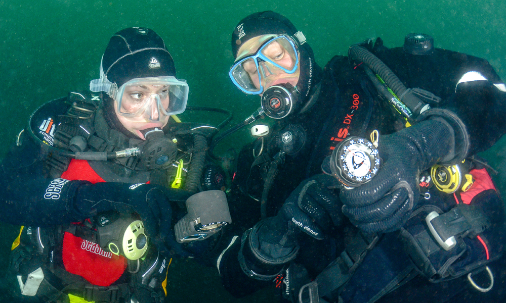 Divers using a compass underwater