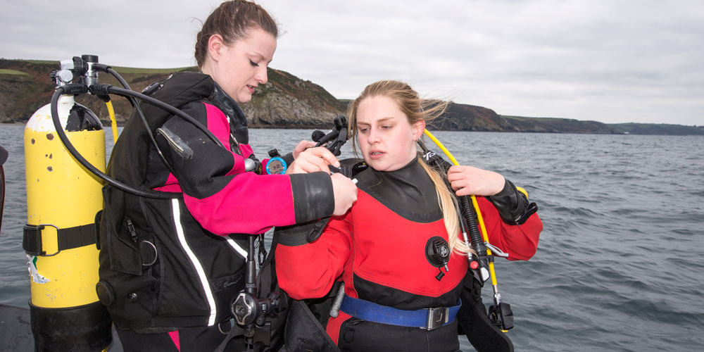 Scuba divers checking buddies kit before getting in the water