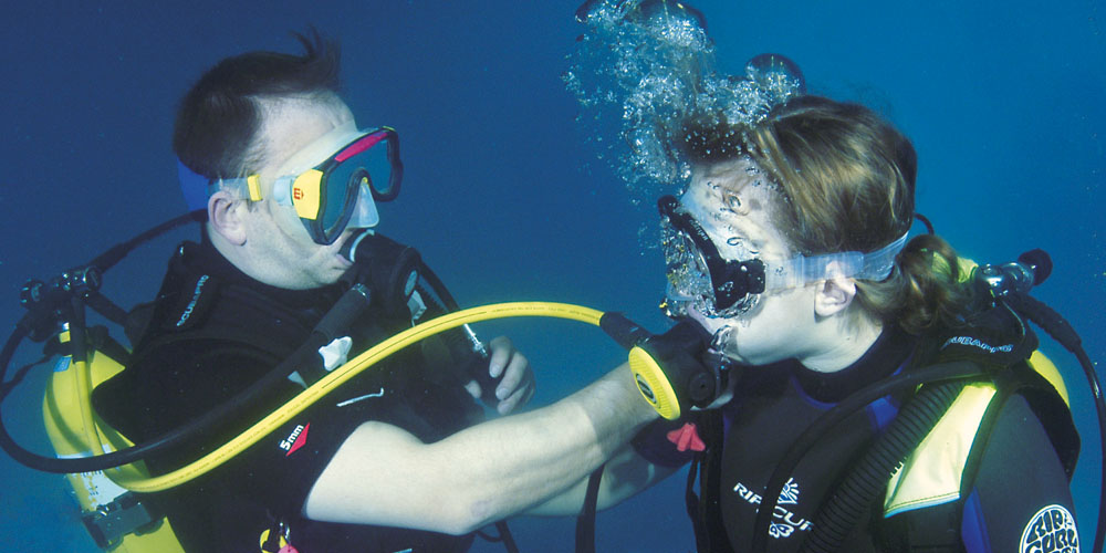 Scuba diving instructor doing refresher skills in the pool