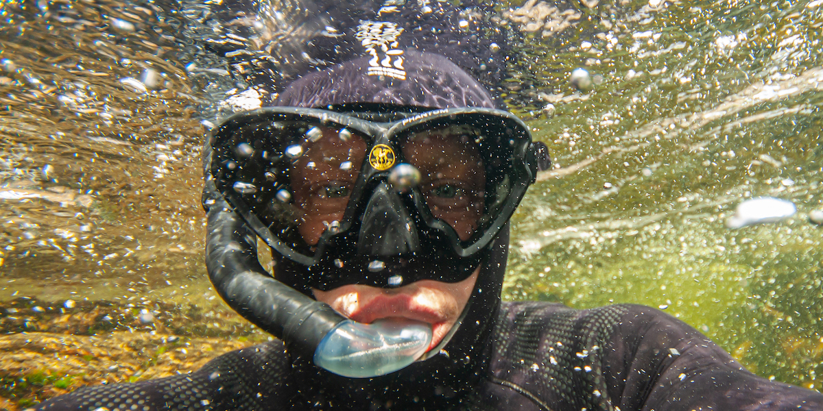 A snorkeller takes a selfie under the surface of the water