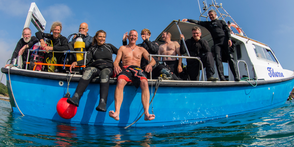 A group of divers on a boat posing for a photograph - looking to camera