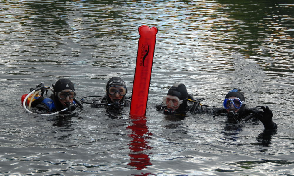 Divers with marker buoy at surface