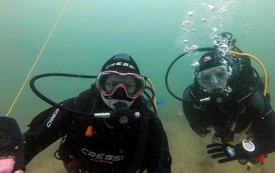 A diver with a reel and their buddy looking at the camera